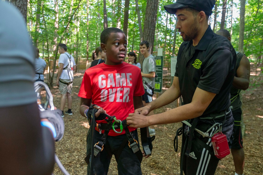 Joshua Heartwell, 11, learns about ropes course safety from Go Ape instructor Dylan Gatete.
