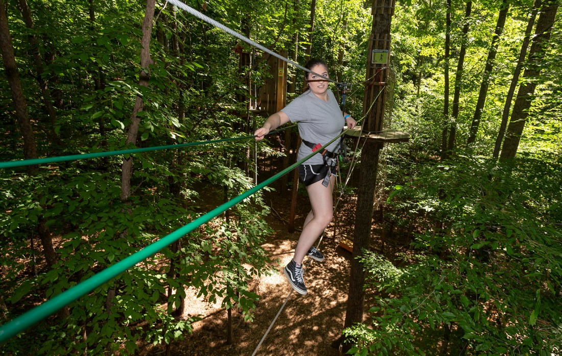 Katelyn Arwood scales a cable between trees at Go Ape in Raleigh.