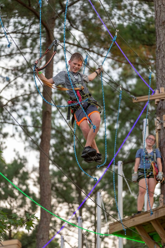 Jay Elliott works to keep his balance walking a tight rope at TreeRunner Raleigh Adventure Park.