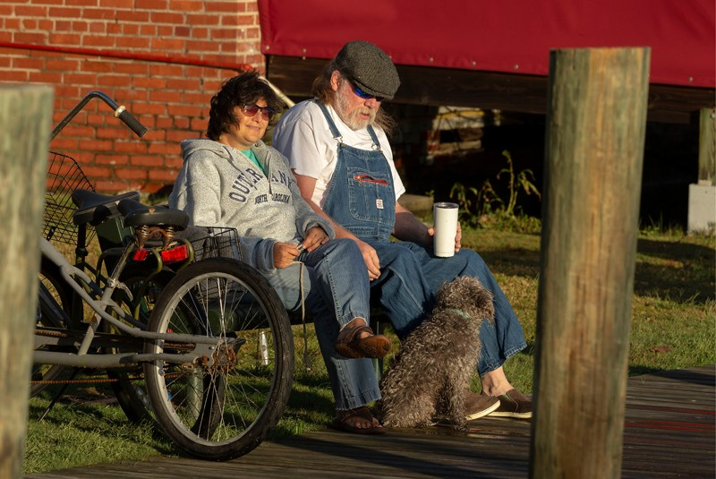 Manteo's waterfront boardwalk is one of the best ways to take in the views of Shallowbag Bay and the historic attractions of downtown Manteo. The boardwalk winds past marshlands, parks, a boathouse, lighthouse, maritime museum, stores and restaurants. At right, long-time Manteo residents Becky and Bill Rea enjoy sunrise with their dog Nala on Manteo Waterfront Marina, which provides overnight and seasonal slip rentals.