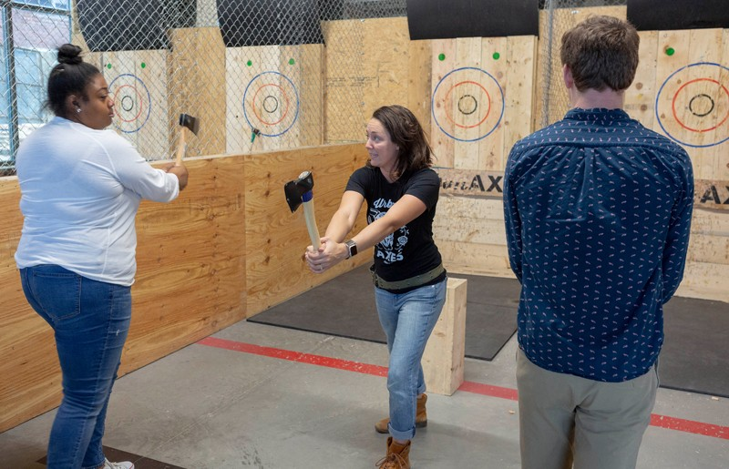 """Urban Axes coach Zoey Best teaches Sequoia Watkins, left, proper ax-throwing technique. Coaches, or """"axperts,"""" enforce safety rules and must be present in the arena when anyone is throwing."""