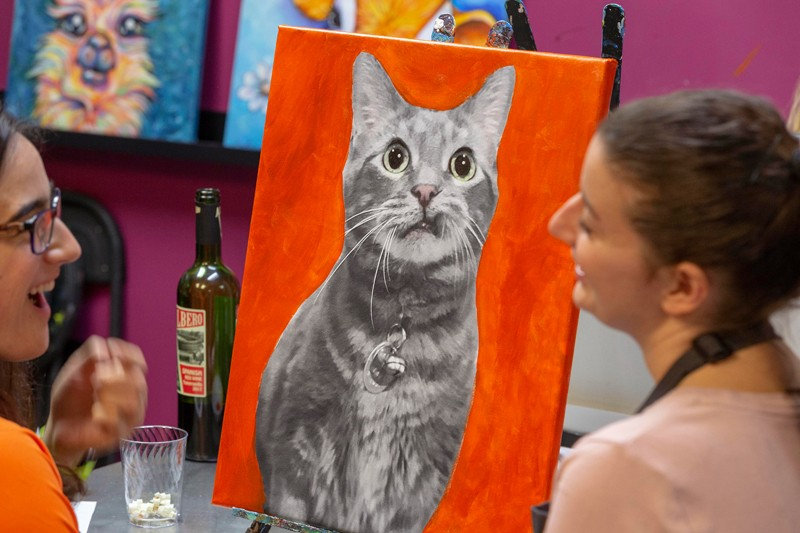 Claire Kane, left, and Elise Hattingh chat during a pet portrait class. Participants began the class with a photo of their pet printed on canvas — ready for them to fill in with paint.