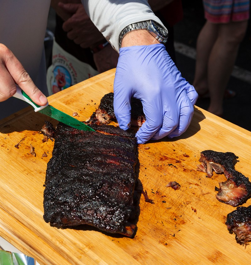 A volunteer with the Withers Ravenel engineering team cuts ribs at the Peak City Pig Fest. The meat was sold to hungry festival attendees to raise money for the Apex Sunrise Rotary Club and its philanthropic efforts.