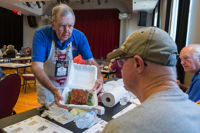Blair Smith of Edgewater, Md., presents a box of ribs so the judges at his table can rate the meat's appearance.