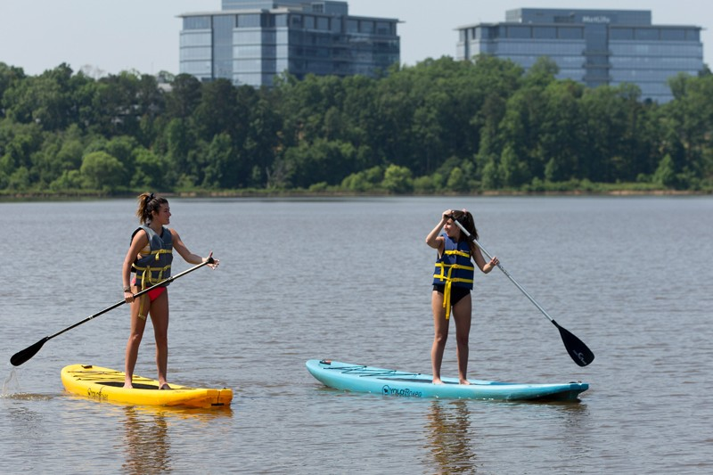 Shelbi Wymard, left, and Emma Golomb explore the shallow waters of Lake Crabtree aboard stand-up paddle boards, which can be checked out for free at the boat dock.