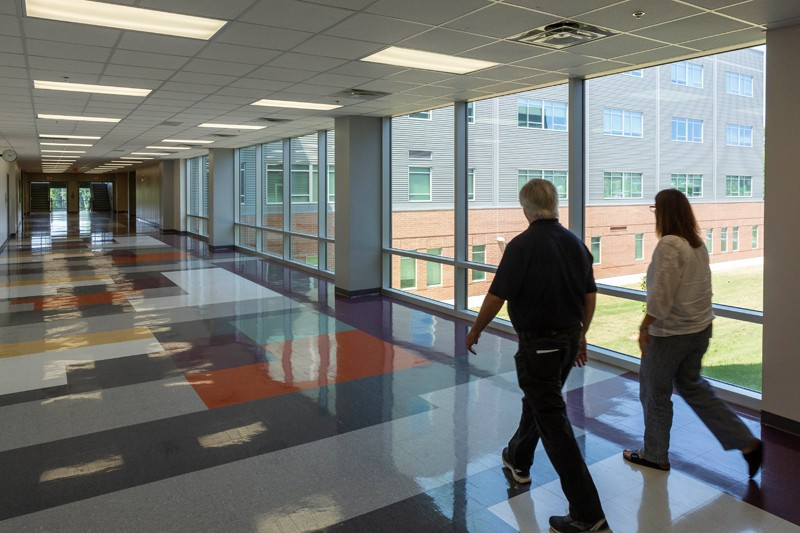 Karen Summers, Green Level principal, and Bill Poston, a spokesman with the Wake County School System, walk down a hallway at the school.