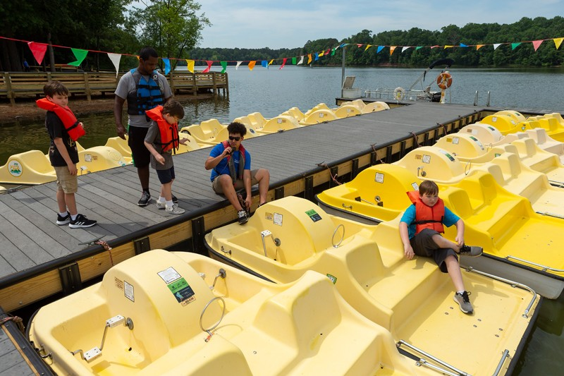 Camp counselor Haileab Fishastion, standing, and boat dock employee Devin Loo load Blake Hampton, left, Phillip Towns, center, and Dylan Douglas onto a pedal boat at Bond Lake.