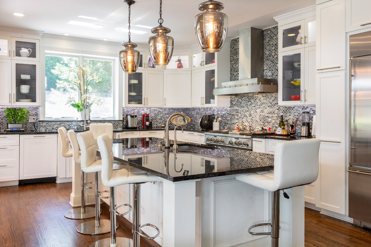 The kitchen had nice cabinetry, but was inefficient and dark. Dawn Christine bumped out the kitchen wall, spun the kitchen island 90 degrees and installed a large window with a thick sill. The grey, white and black color scheme also fit with the clients' modern tastes.