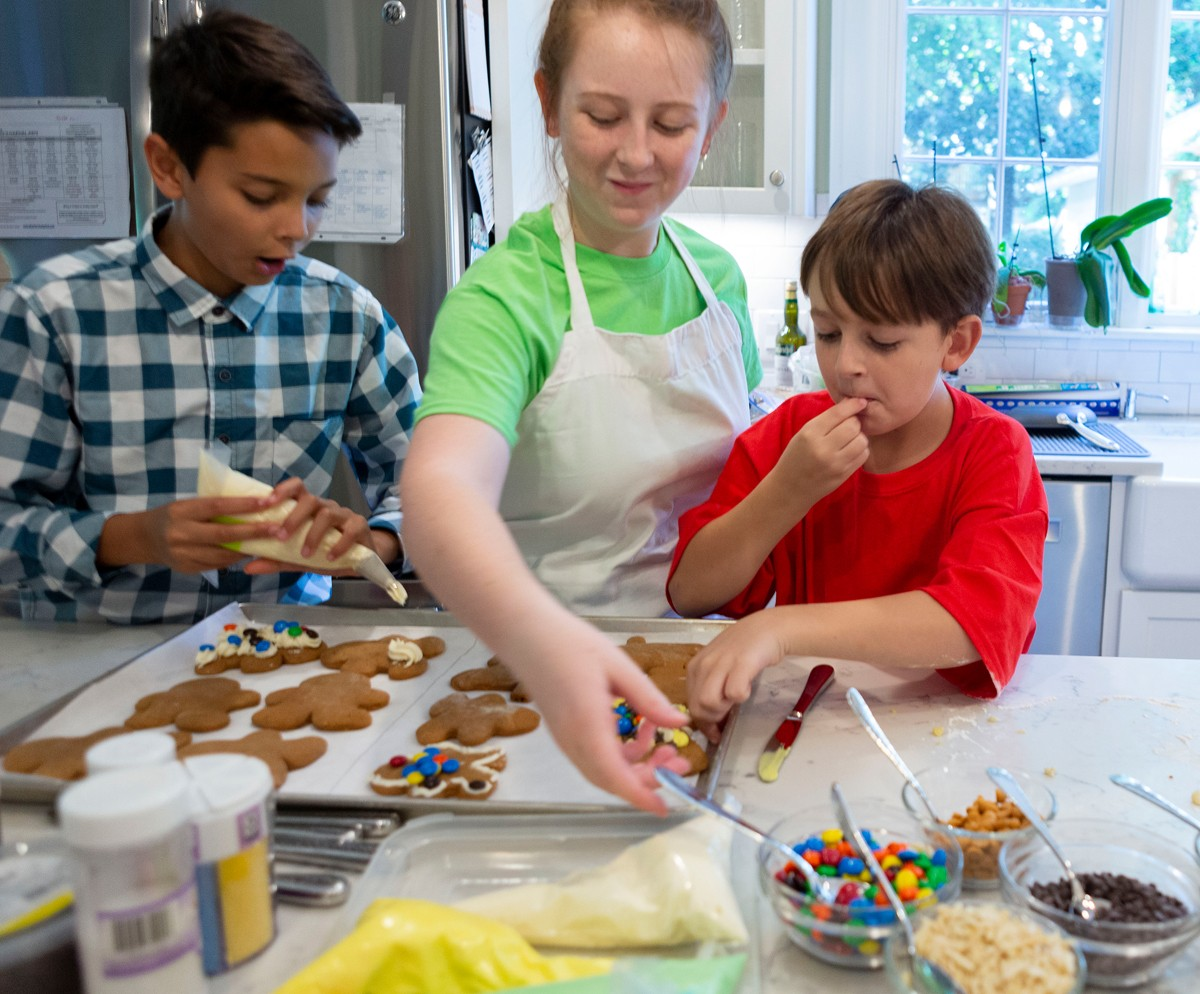 Hunter Tenney, 10, right, samples a few M&M candies, as Kieran Sonbuchner, 11, left, and Cecilia Tenney, 16, decorate gingerbread people.