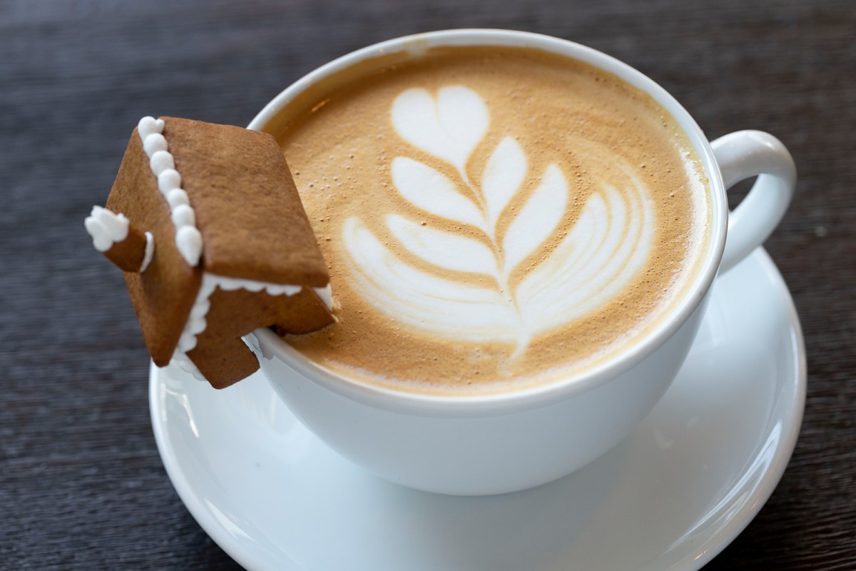 A miniature gingerbread house is a seasonal garnish for lattes and other coffee drinks.