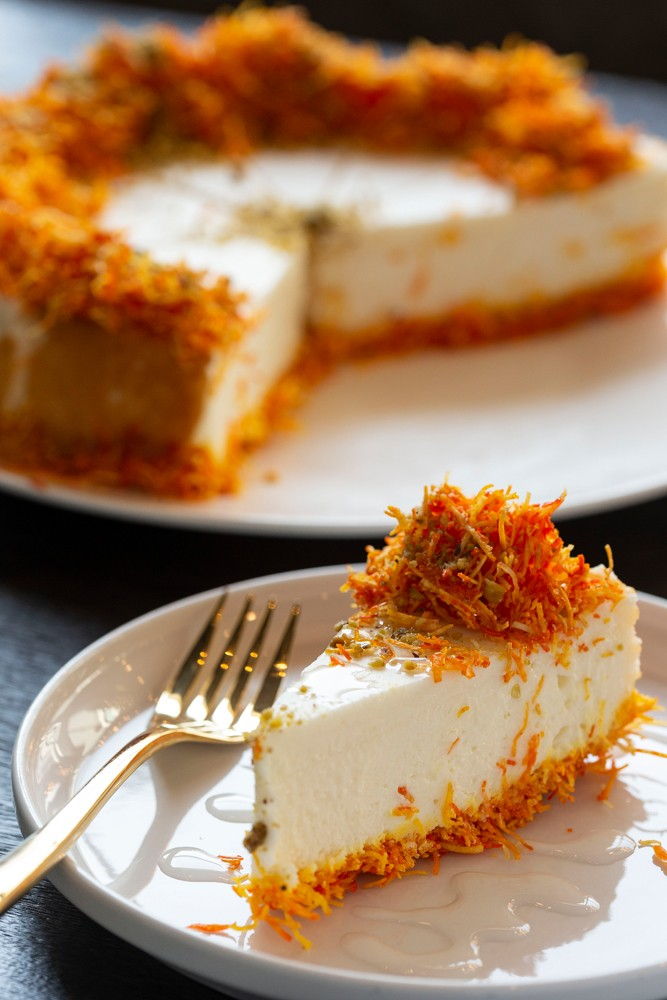 The kunafa cheesecake trades the typical graham cracker crust with a shredded phyllo dough crust and includes a shredded phyllo garnish, crushed pistachios and sweet syrup.