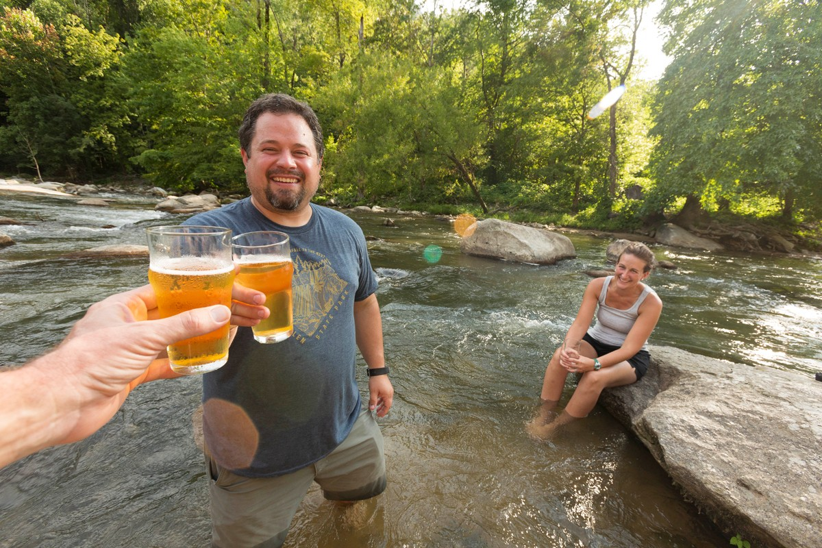 Zach and Nicole Horn of Fletcher, N.C., enjoy craft beers while cooling their feet in the Rocky Broad River in Chimney Rock.